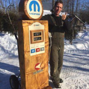 Man standing beside gas pump wood carving