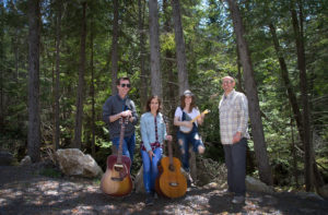 Four band members with guitars in the forest